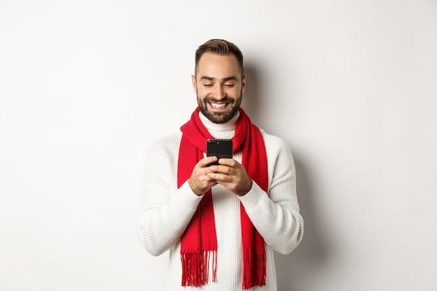 携帯電話でメッセージを読んで、白い背景の上の冬のセーターと赤いスカーフに立って笑っている幸せな男