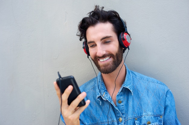 Happy man smiling with mobile phone and headphones