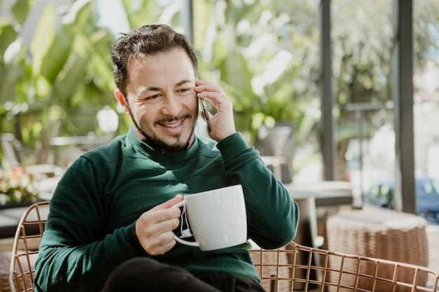 カフェで電話で話す幸せな男