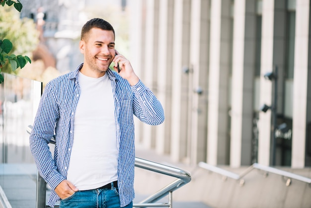 Happy man speaking on phone near banister
