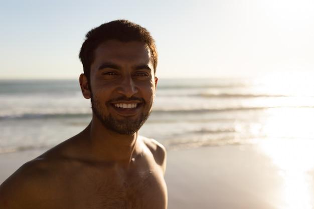 Happy man standing on the beach