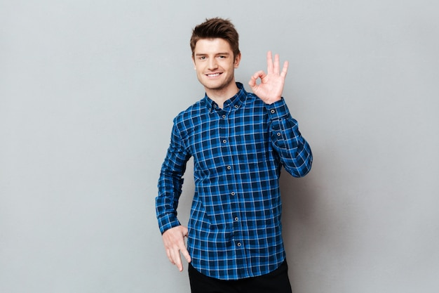 Happy man standing over grey wall and showing okay gesture