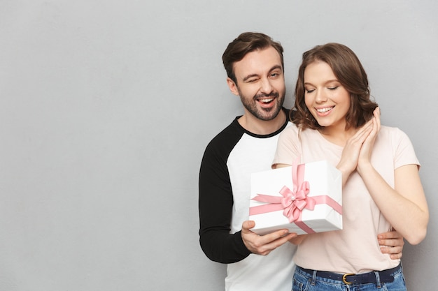 Happy man standing isolated holding present gift box for his woman.