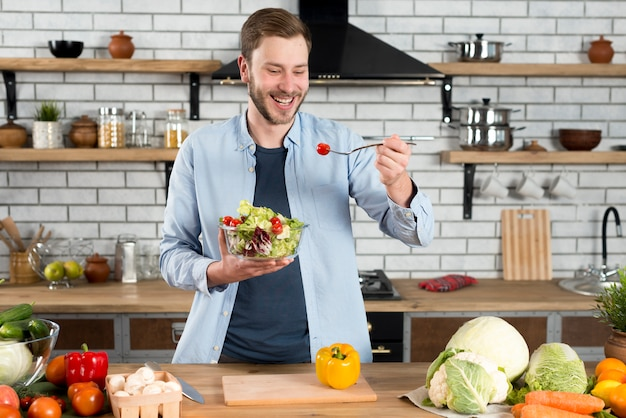 Happy man standing in the kitchen eating fresh salad with fork