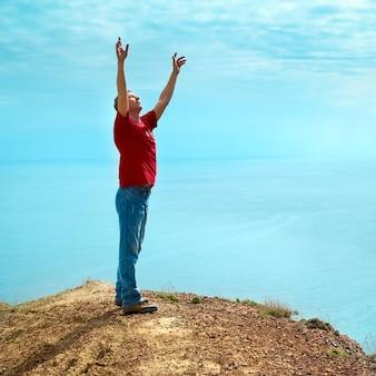 Счастливый человек, стоящий на скале с поднятыми руками, глядя на море