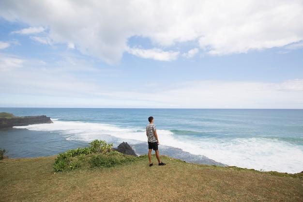 Счастливый человек, стоящий на вершине горы, глядя на океан. успех, победитель, счастье.