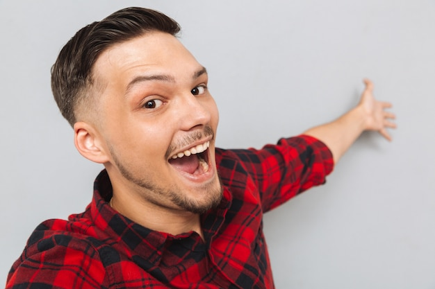 Happy  man standing sideways and posing in studio