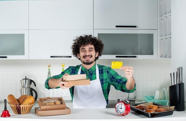 Uomo felice in piedi dietro il tavolo con vari pasticcini e con in mano scatole marroni di carte bancarie nella cucina bianca