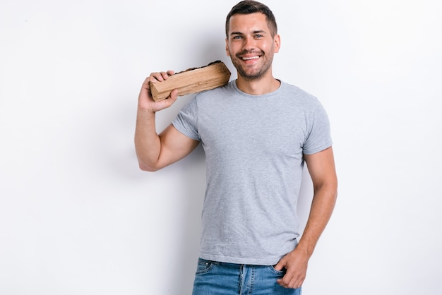 Happy man standing over white studio background and holding a firewood on his shoulder. studio image, isolated on white background