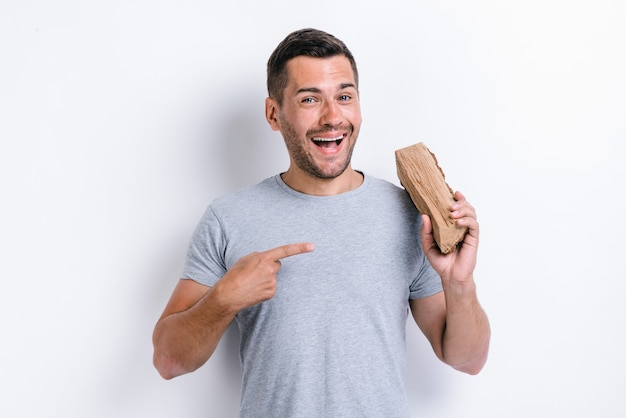 Happy man standing over white studio background and pointing at firewood while holding it on his shoulder. studio image, isolated on white background