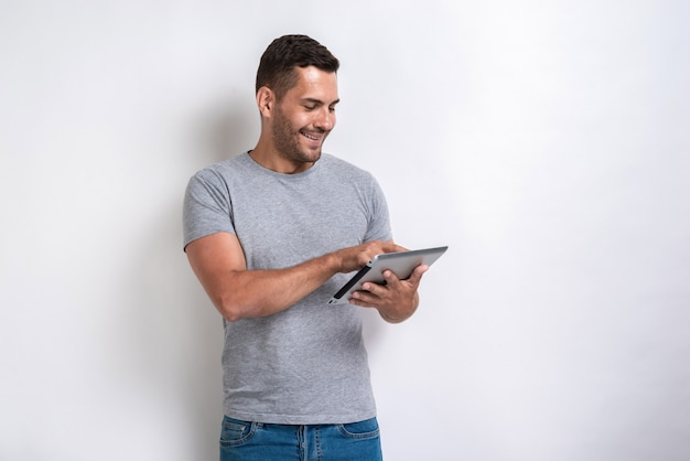 Happy man standing with ipad looking at the screen of it.