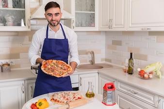ピザの台所で立っている幸せな男