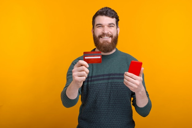Happy man standing over yellow wall and showing his credit card and holding smartphone