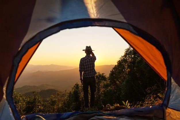 幸せな男は、レジャーと自由を楽しんで夕焼けの光の空の下で山の周りのテントの近くに滞在します。