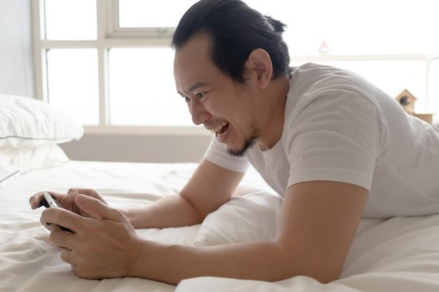 Счастливый человек остается дома и играет в мобильную игру в своей квартире