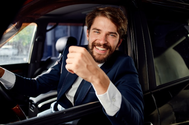 Happy man in suit looks out of the car window and gestures with his hands