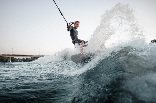 青い水の下でボードをサーフィンする幸せな男