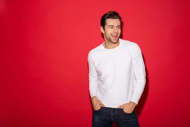 Happy man in sweater looking away with arms in pockets over red wall