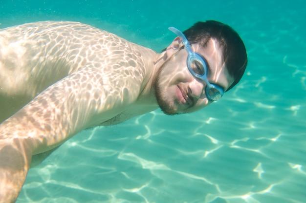 イオニア海、ザキントス、ギリシャ、水中シーンで泳いで幸せな男