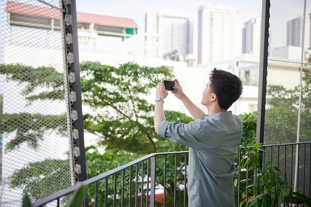 Счастливый человек фотографирует с мобильным телефоном, стоящим на открытом воздухе