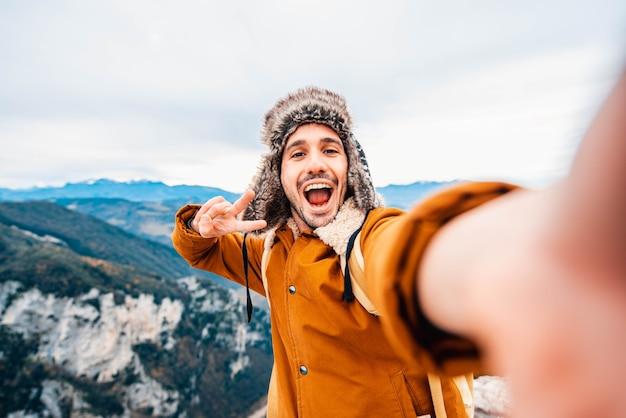 Happy man taking a selfie climbing mountains