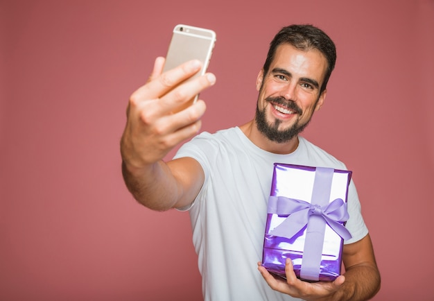 Happy man taking selfie with cellphone holding gift box