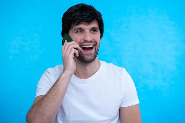 スマートフォンで話し、目をそらして幸せな男