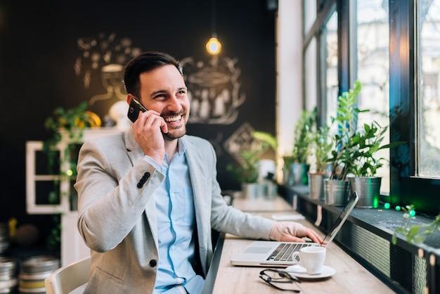 Happy man talking over mobile or smartphone. handsome man working in restaurant.