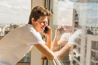 Happy man talking on smart phone in front of glass window