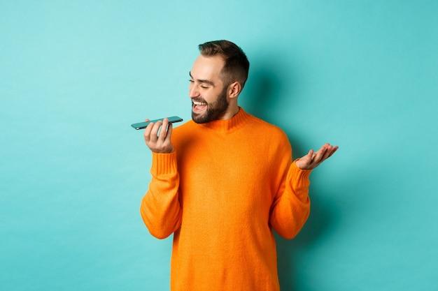 밝은 파란색 배경 위에 주황색 스웨터에 서 스피커폰, 몸짓 및 휴대 전화에 음성 메시지를 녹음에 대 한 얘기 행복 한 사람.