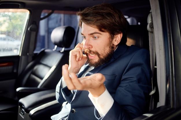 자동차 초상화에 전화 통화하는 행복 한 사람은 소송을 닫습니다.