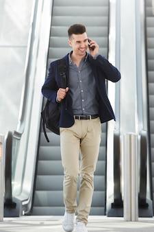 Happy man on telephone call by escalator