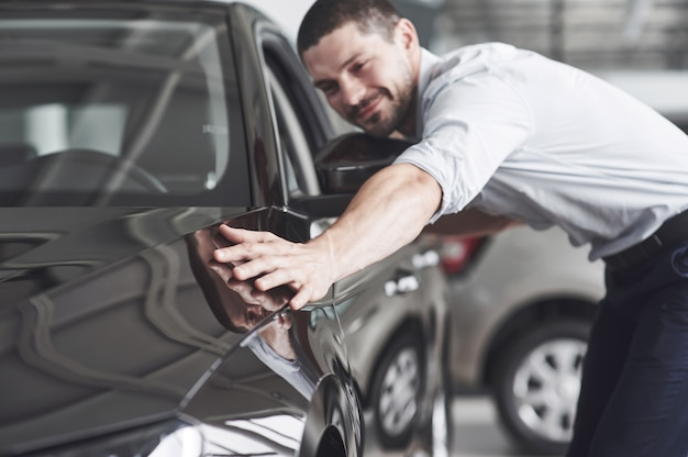 Happy man touching car in auto show or salon.