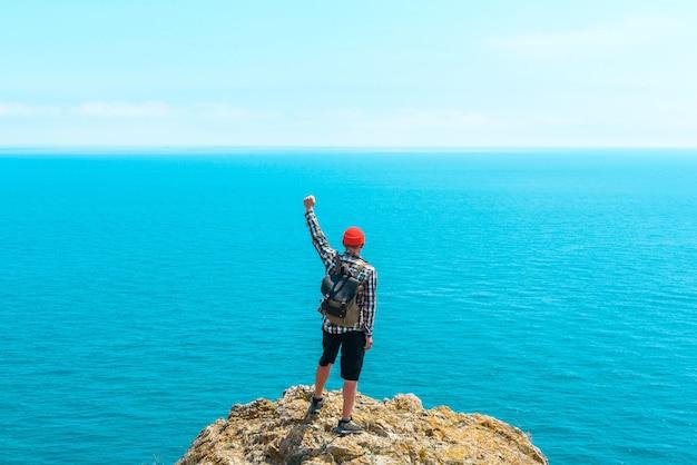 배낭을 메고 즐겁게 손을 들고 여름에 아름다운 바다를 바라보는 행복한 남자