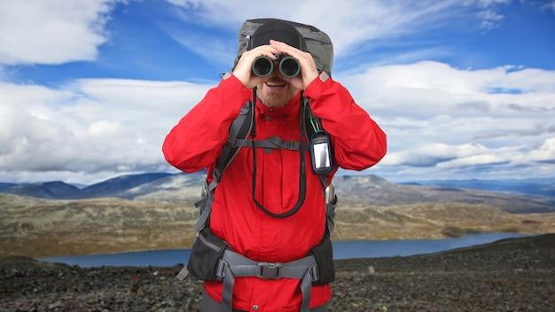 산 표면에 손에 쌍안경으로 행복한 사람 여행자