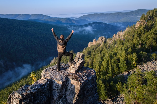 Happy man traveller standing with raised hands on mountain top and celebrating success