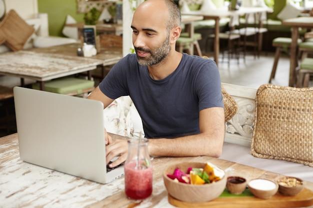 Happy man typing message on laptop while having fresh smoothie at sidewalk restaurant.