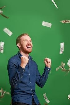 Счастливый человек под дождем на деньги