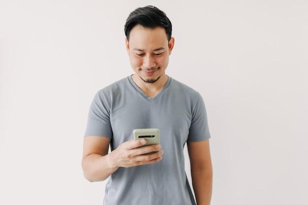 幸せな男は白い壁に分離されたスマートフォンを使用します