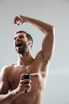 Happy man using deodorant