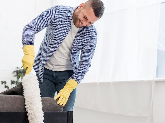 Happy man using a duster