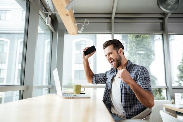 Счастливый человек, используя портативный компьютер, держа телефон.