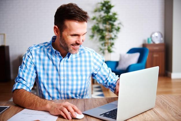 彼のホームオフィスでラップトップを使用して幸せな男