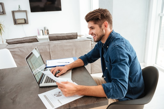 Happy man using laptop and sitting at the table while looking at the papers