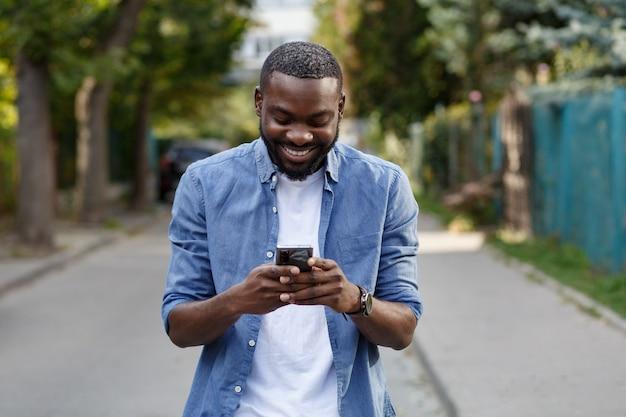 携帯電話アプリ、テキストメッセージ、インターネットの閲覧、スマートフォンの閲覧を使用して幸せな男