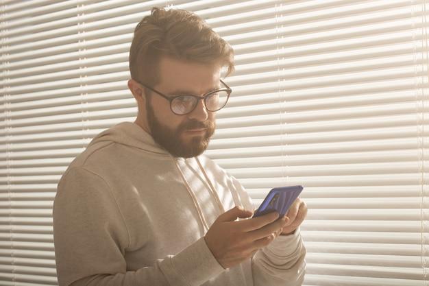 自宅やオフィスで携帯電話を使用して幸せな男