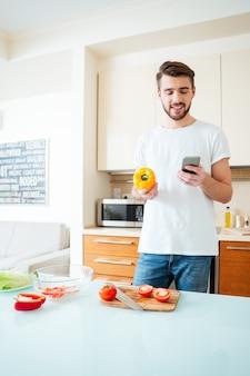 キッチネでスマートフォンを使用して幸せな男