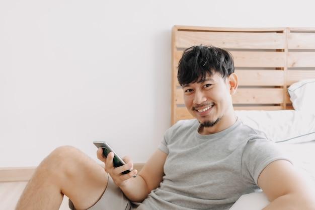 아파트에서 휴식을 취하는 동안 스마트폰을 사용하는 행복한 남자