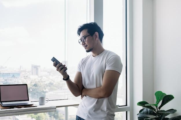 Счастливый человек, использующий смартфон с балконом, концепция работы из дома
