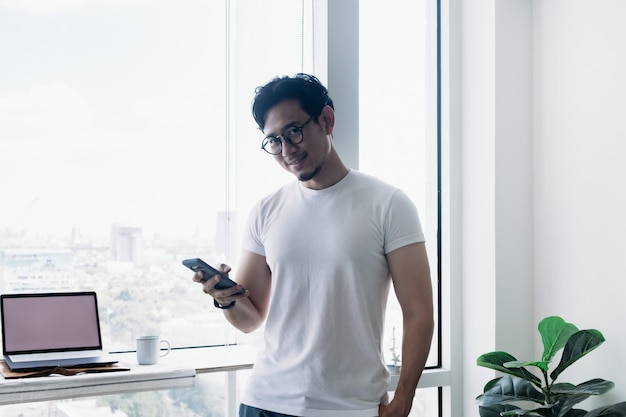 Happy man using smartphone with balcony view concept work from home